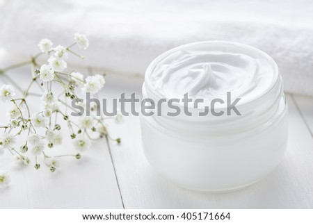 Anti wrinkle anti-aging cosmetic cream skincare and face care moisture lotion with herbal flowers in glass jar with towel on white background - stock photo