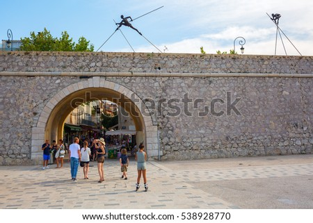 Antibes, France - July 24, 2016: city gate at the historic city wall with unidentified people. Antibes is a Mediterranean resort in Alpes-Maritimes department of southeastern France, on Cote d Azur