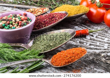 Antic metal spoons and small bowl with different kinds of spices, sea salt and red hot chili peppers, bunch of cherry tomatoes and herbs on old wooden board. Selective focus. - stock photo