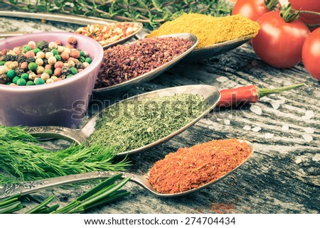 Antic metal spoons and small bowl with different kinds of spices, sea salt and red hot chili peppers, bunch of cherry tomatoes and herbs on old wooden board. Selective focus. Toned. - stock photo