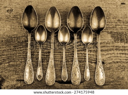 Antic metal spoons on old wooden board. Selective focus. Toned. - stock photo