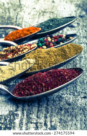 Antic metal spoons with different kinds of spices on old wooden board. Selective focus. Toned. - stock photo