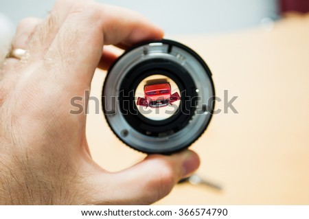 Anticipation of a new dream car - man holding camera lens with the new car inside - stock photo