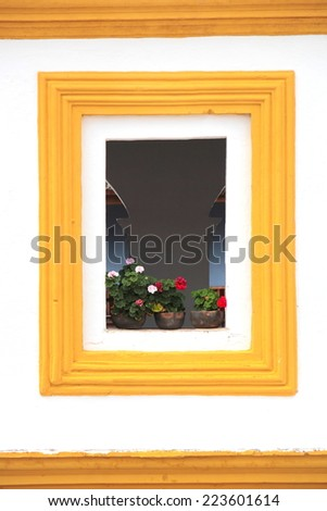 Antigua, Guatemala: beautiful window with flowers in the old streets of Antigua, the former colonial capital of the country. - stock photo