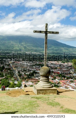 Antigua, Guatemala â?? June 16, 2011:Cerro de la Cruz is a religious stone cross monument placed where you can overlook the city of Antiqua in Guatemala with the Agua volcano in the background.