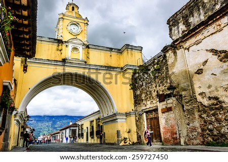 Antigua, Guatemala - November 19, 2014: Locals walk in street of Santa Catalina Arch & ruins in Spanish colonial town & UNESCO World Heritage Site. Agua volcano hides behind cloud. - stock photo