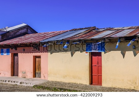 Antigua, Guatemala - October 5, 2014: Old, colorful, painted houses adorned with Guatemalan flags in colonial city & UNESCO World Heritage Site of Antigua.