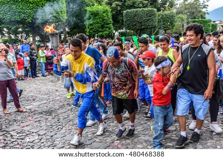 Antigua, Guatemala - September 14, 2015: Locals run in streets with lit torches while blowing whistles & horns during Guatemalan Independence Day celebrations
