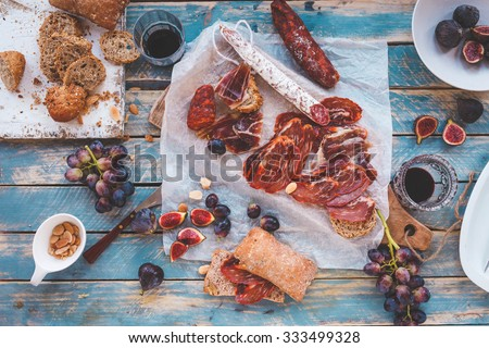 Antipasti and fruit concept. Tasting gourmet party on a rustic wooden table. A quick and easy snack for party time. Rustic style. - stock photo
