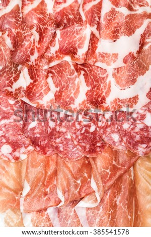 Antipasti composition of italian cured meat types. Salami, ham and Prosciutto di Parma slices, closeup and top view, vertical. Food background, texture and wallpaper - stock photo