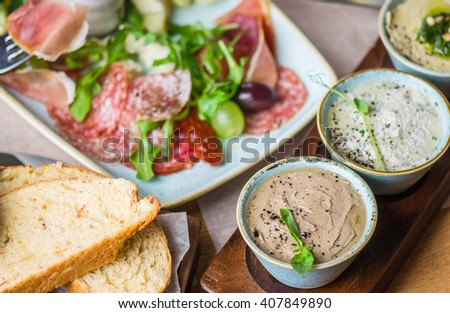 Antipasti - Italian appetizer of meat, sausages , pate , fish Rieti , hummus and arugula . Close- up of a plate on a restaurant table .  - stock photo