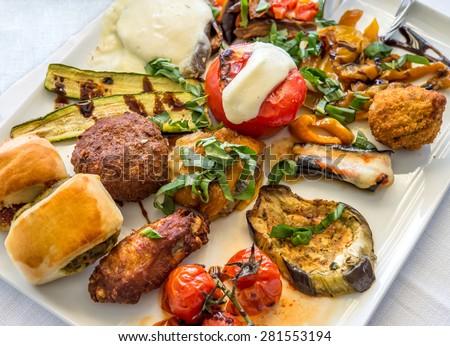 Antipasti on white plate in Italian restaurant. - stock photo