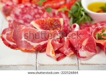 antipasti Platter of Cured Meat,   jamon, sausage, salame  on textured white wooden table - stock photo