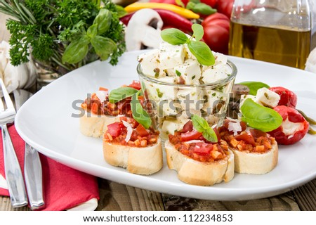 Antipasto (Bruschetta and Feta) with ingredients in the background on wood