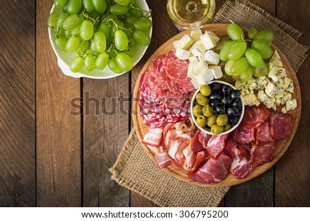 Antipasto catering platter with bacon, jerky, salami, cheese and grapes on a wooden background. Top view - stock photo