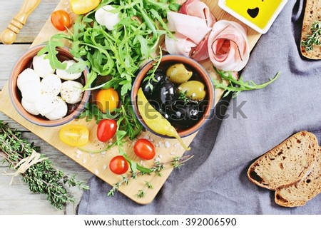 Antipasto concept  including mozzarella cheese,olives and ham with tomatoes and arugula.Selective focus. - stock photo