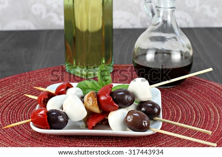 Antipasto on a skewer.  Skewers include Italian olives, roasted peppers and garlic with mozzarella cheese.