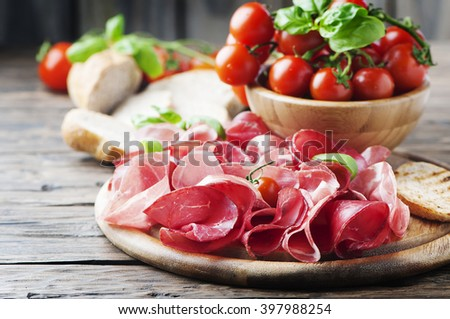 Antipasto with ham and bresaola, selective focus - stock photo