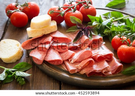Antipasto with ham, bresaola and salami. bread, tomato and basil. selective focus. - stock photo