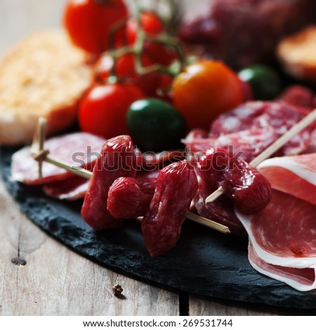 Antipasto with ham, olive and tomato on the wooden table, selective focus and square image - stock photo