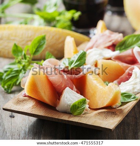 Antipasto with melon, mozzarella, ham and basil, selective focus and square image