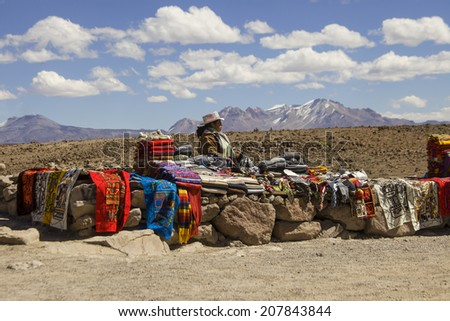 ANTIPLANO,PERU - JULY 13, 2014: An unidentified woman selling handicrafts outdoors July 13, 2014  on the plains in Peru. Many women work selling handicrafts in Peru  - stock photo