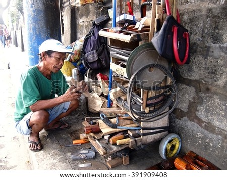ANTIPOLO CITY, PHILIPPINES - MARCH 15, 2016: A man sells a variety of hand made carpentry tools along a street in Antipolo City, Philippines