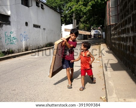 ANTIPOLO CITY, PHILIPPINES - MARCH 15, 2016: A young boy carries a piece of wood as his younger companion looks on and talks to him. - stock photo