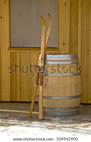 Antiquated pair of skis leaning against a wooden barrel. With space for copy - stock photo