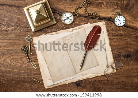 antique accessories and office supplies on wooden table. vintage keys, clock, glasses, feather pen, compass. nostalgic sentimental background - stock photo