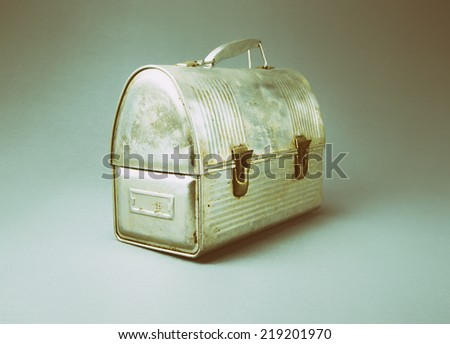 Antique aluminum lunch box against gray background.  Analog filter - stock photo