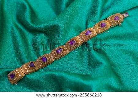 Antique amethyst bracelet placed on a teal fabric. - stock photo