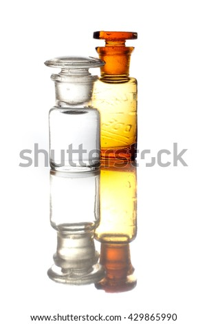 Antique and vintage glass bottles for pharmaceutical use isolated on a white background with reflections. - stock photo