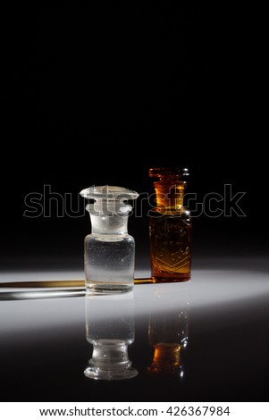 """Antique and vintage glass bottles for pharmaceutical use of """"Teinture d'iode"""" (means Tincture of iodine), that is an antiseptic medicine, isolated on a dark background. - stock photo"""