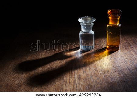 """Antique and vintage glass bottles for pharmaceutical use of """"Teinture d'iode"""" (means Tincture of iodine), that is an antiseptic medicine, isolated on a wooden background. - stock photo"""