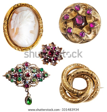 Antique and well worn gold jewelry - cameo,  amethyst, enamel, garnet and three-ring (lover's knot) gold brooches - stock photo