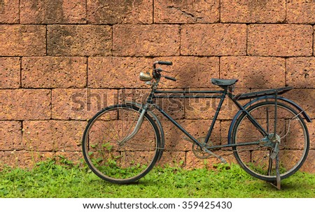 Antique bicycle on brick wall - stock photo