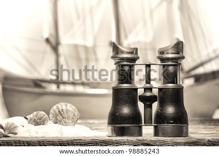 Antique binocular on an old seashore resort wood pier deck with seashells on sand and a vintage wooden tall sail ship sailing by at sea at the shore