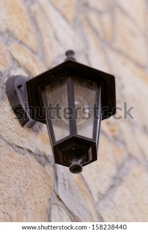 antique black lantern side by building (stone wall)