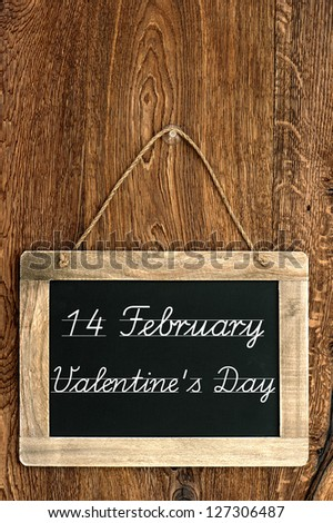 antique blackboard on wooden wall with sample text 14 February Valentine's Day. vintage background
