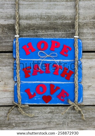 Antique blue sign with red HOPE, FAITH, LOVE and heart hanging by braided rope on rustic wood background - stock photo