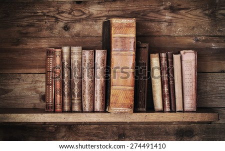 antique books on old wooden shelf. - stock photo