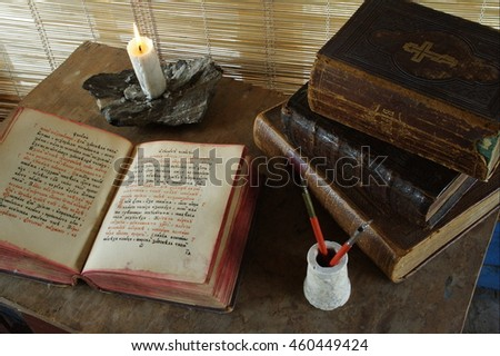 Antique books opened for reading with ancient lamp