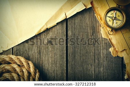 Antique brass compass and rope over old map - stock photo