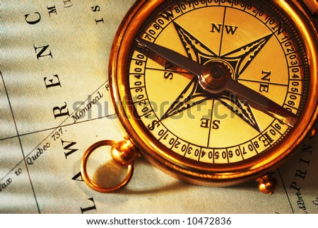 Antique brass compass over old Canadian map background - stock photo