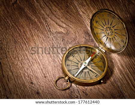 Antique brass compass over wooden background