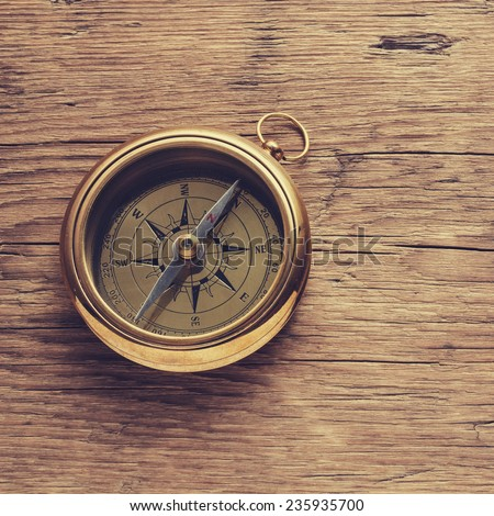 Antique brass compass over wooden background  - stock photo