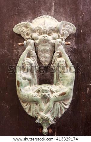 Antique brass door knocker on a lacquered wooden door in Malta - stock photo