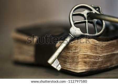 Antique brass key on old leather-bound book.  Shallow depth of field. - stock photo