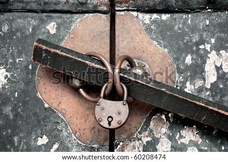 Antique brass lock on textured metal door - stock photo